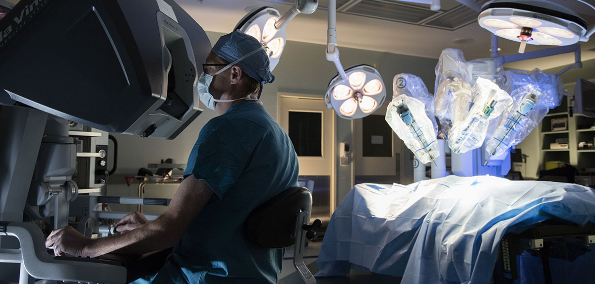 Surgeon sitting in front of monitor in surgical suite