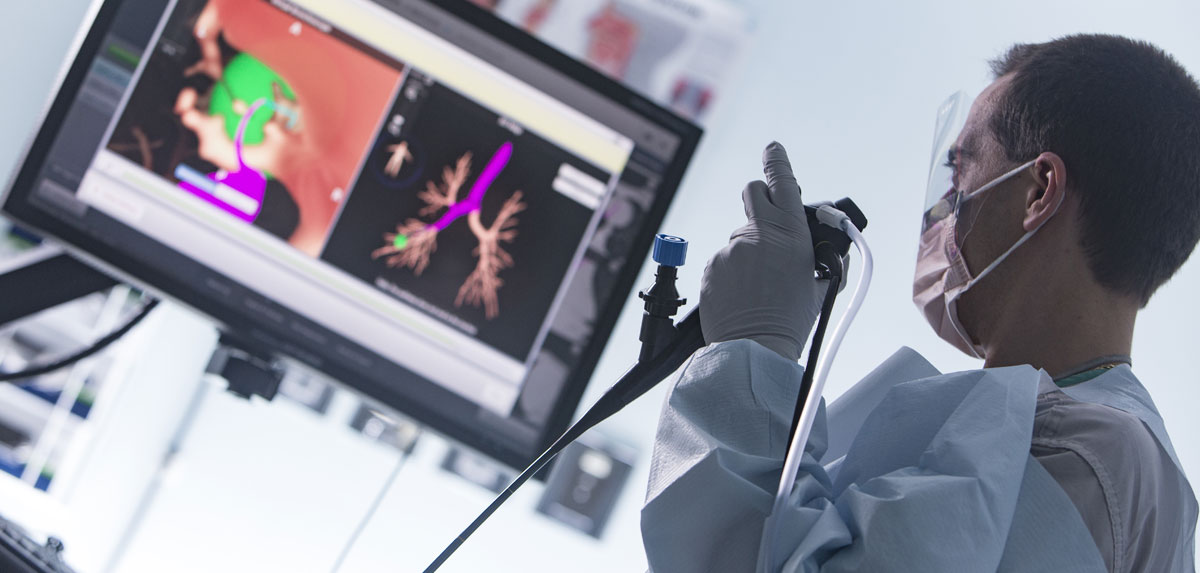 Doctor using scope and looking at monitor